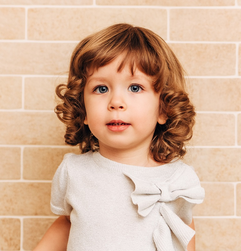 toddler girl's curly hair with bangs