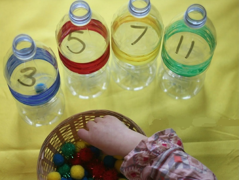 Color pom poms in a water bottle