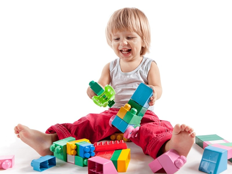3 years old child is playing with lego